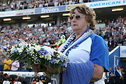 Liz Costa, chairperson of Brighton supporters club, with a wreath as part of the tribute to Matt Grimstone and Jacob Schilt who were killed in the Shoreham air disaster during the Sky Bet Championship match between Brighton and Hove Albion and Hull City at the American Express Community Stadium, Brighton and Hove, England on 12 September 2015. Photo by Bennett Dean.