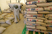 The Breidjing Refugee Camp, Eastern Chad on the Sudanese border shelters 30,000 people who have fled their homes in Darfur, Sudan. Men move bags of donated and purchased grain which is handed out to the refugee families who are organized into blocks every month by the United Nations WFP (World Food Program). (Supporting image from the project Hungry Planet: What the World Eats.)