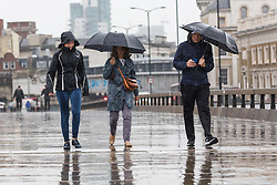 © Licensed to London News Pictures. 27/07/2019. London, UK. People walk across London Bridge during heavy rain this morning. London and the UK are experiencing heavy rain and stormy weather today following the heatwave and record temperatures during the week. Photo credit: Vickie Flores/LNP