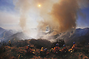 Nuclear Winter test fire: fire crews rest while monitoring the brown smoke rising from smoldering brush fires, deliberately started to study the potential climatic effects of a nuclear war. The nuclear winter theory predicts that smoke from fires burning after a nuclear war would block sunlight, causing a rapid drop in temperature that would trigger serious ecological disturbance. The test burn took place in December 1986 on 500 acres of brush in Lodi Canyon, Los Angeles. Dripping napalm from a helicopter ignited the fire. Ground-based temperature sensors were used to study soil erosion. Various airborne experiments included smoke sampling & high-altitude infrared imaging from a converted U-2 spy plane.