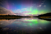 A vivid display of Northern Lights reflects in the waters of the New Meadows wetland in West Bath, Maine.