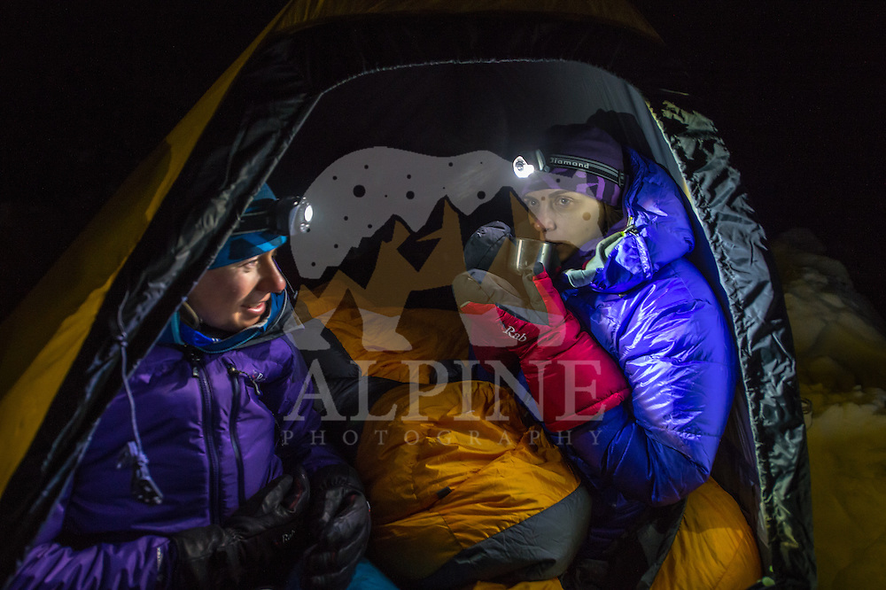 A female mountaineer drinks a warm tea from a thermos on a cold winter night in Mont Blanc Massif.