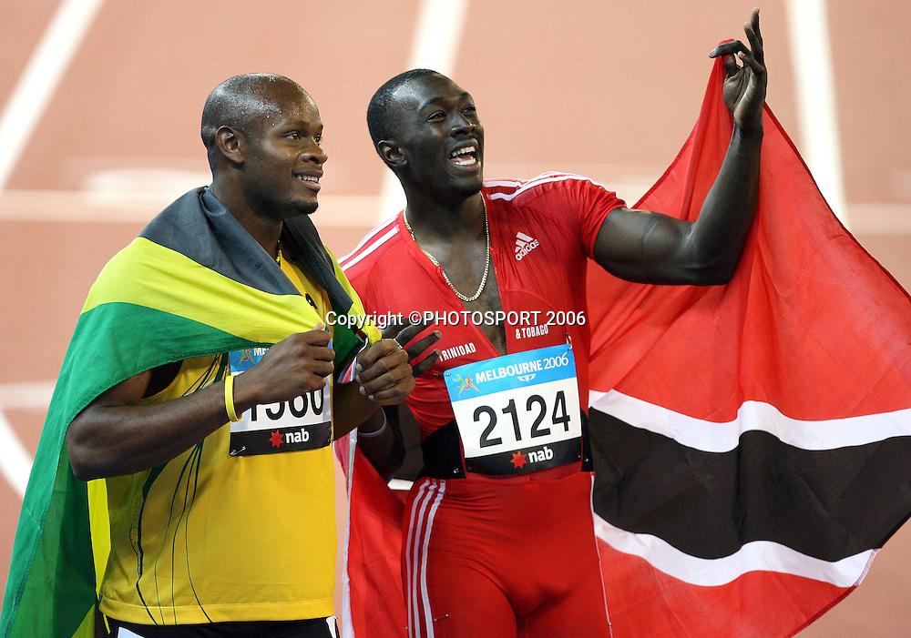 Jamaican athlete Asafa Powell (JAM) celebrates with Trinidad's Marc Burns (TRI) after winning the Men's 100M sprint on Day 5 of the XVIII Commonwealth Games at the MCG, Melbourne, Australia on Monday 20 March, 2006. Photo: Hannah Johnston/PHOTOSPORT<br /><br />150697 jamaica trinidad celebration sportsmanship