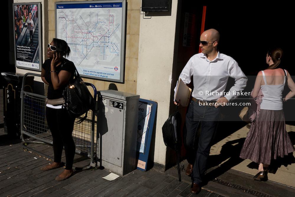 Londoners wearing sunglasses outside Sloane Square underground station.