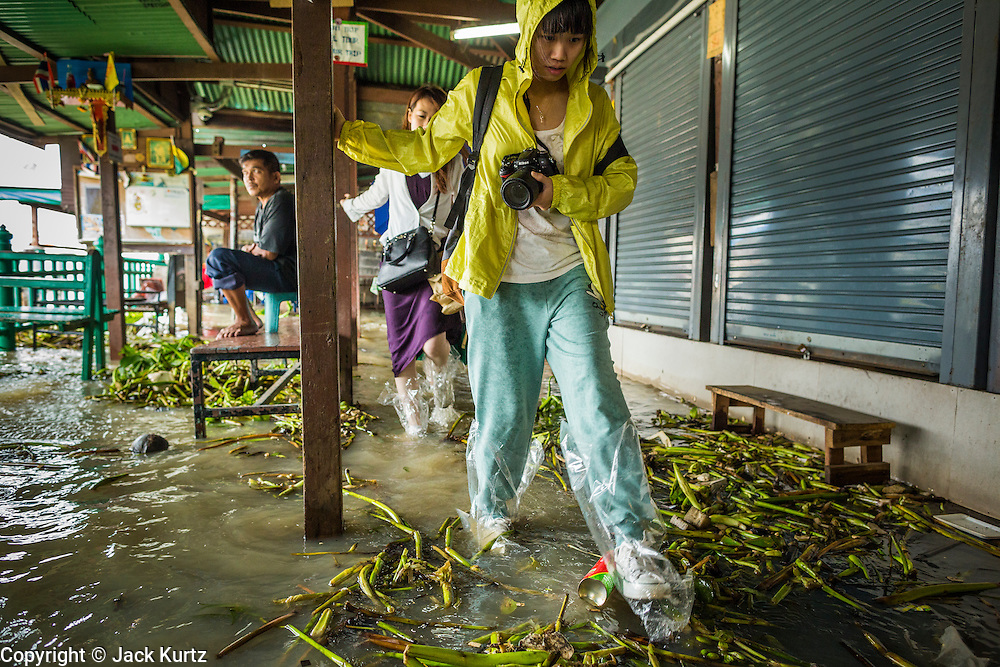 23 SEPTEMBER 2013 - BANGKOK, THAILAND: Tourists walk through floodwaters towards shore after getting off a Chao Phraya River Express Boat at Tha Tien Pier on the Chao Phraya River in Bangkok. More than a quarter of the provinces in Thailand are reporting some flooding as heavy rainy season storms continue in central Thailand. Rain is expected to continue through this week, raising the possibility of serious flooding throughout the country. More than 600,000 Thais have been impacted by the flooding so far this year. Flooding in 2011 killed more than 800 people and cut economic growth for the year to just .10 percent.     PHOTO BY JACK KURTZ