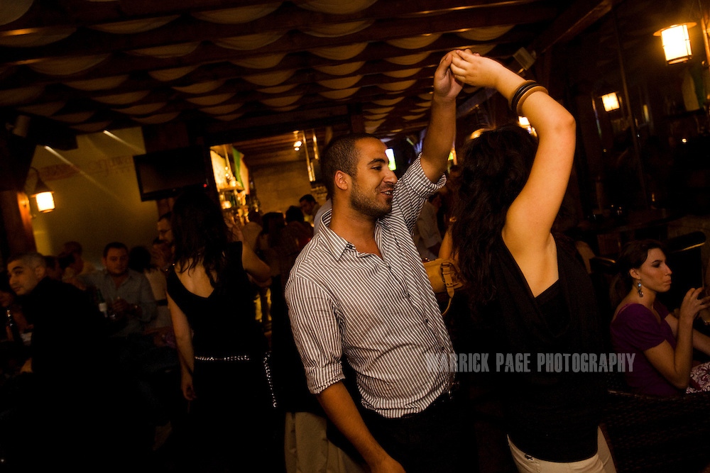 RAMALLAH, WEST BANK - JUNE 24: A Palestinian couple dance in the Orjuwan Lounge, on June 24, 2010, in Ramallah, West Bank. Nightlife in Ramallah is on the rise as numerous restaurants and bars are opening throughout the de facto capital of the West Bank, as economic growth has been steady since 2007 in spite of the ongoing occupation. NGO workers, international travellers and the youth of Palestine's elite, are flocking to the city's cosmopolitan scene, in-part due to the growth of venues, but also due to the restrictions on movement enforced by the Israeli occupation limiting options. (Photo by Warrick Page)