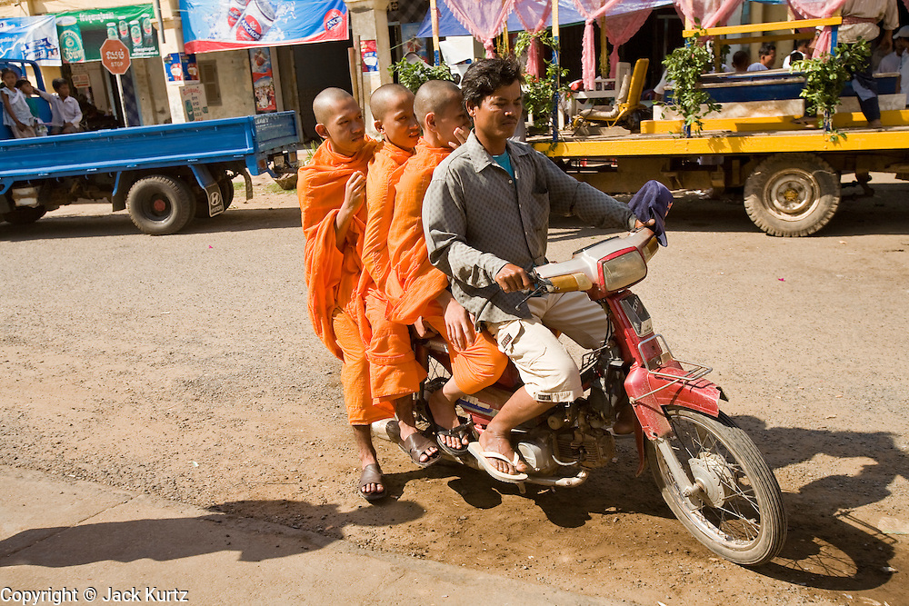 16 MARCH 2006 - KAMPONG CHAM, KAMPONG CHAM, CAMBODIA: Buddhist monks on the back of a motorcycle in the city of Kampong Cham  in central Cambodia on the Mekong River. Motorcycles are frequently used as taxis in rural southeast Asia.  PHOTO BY JACK KURTZ