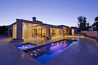 Exterior of modern home with swimming pool at dusk