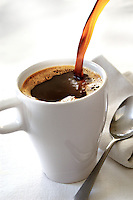 Pouring a fresh cup of american coffeee, spoon on side