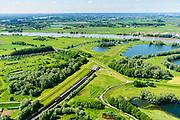 Nederland, Gelderland, Duiven, 29-05-2019; Groessen, natuurgebied Kandia. Betuweroute met vrachttrein, verlaat de tunnel. Met dienstgebouw van de tunnel onder het Pannerdensch kanaal.  Neder-Rijn in de achtergrond.<br /> Tunnel Betuweroute, freight railway, Pannerdensch channel (Lower Rhine) on the horizon.<br /> luchtfoto (toeslag op standard tarieven);<br /> aerial photo (additional fee required);<br /> copyright foto/photo Siebe Swart