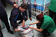 AFC Wimbledon defender Will Nightingale (5) handing out presents delivering Christmas presents to the children on behalf of AFC Wimbledon, at St George's Hospital, Tooting, United Kingdom on 13 December 2018.