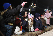 Pine Bush, NY - Children watch a performer take the outdoor stage during the Pine Bush Festival of Lights on Main Street on the evening of Dec. 1, 2007.