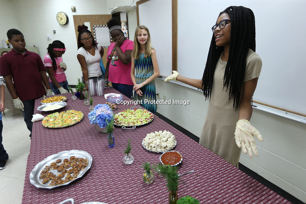 Leah Headson, 11, practices describing the food in front of her classmates before their guests enter for a lunch break.