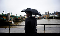 © Licensed to London News Pictures. 29/08/2012. London,UK. People with umbrellas walk along Millenium Bridge in the Rain in Central London today 29th August 2012 .Photo credit : Thomas Campean/LNP.