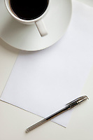 High angle view of coffee cup with pen on a blank paper