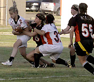 Junior Sam Harp (2,) senior Brittany Tonne (8) and junior Stephanie McCormick (32) battle for the ball during the 3rd Annual Powderpuff Challenge, the junior girls (class of 2008) against the senior girls (class of 2007.)