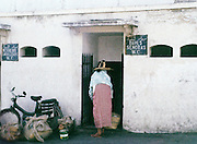 AFRICA; MOROCCO; TANGIER:  Moroccan Berber woman in traditional dress entering women's public restroom with signs in Arabic, French, Spanish and English.