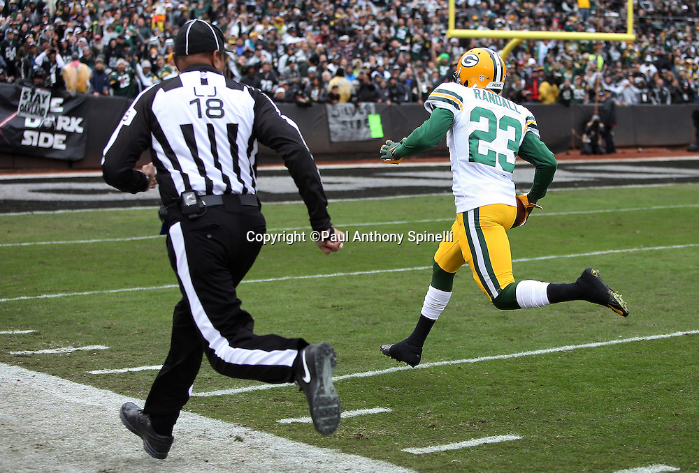 Line judge Byron Boston (18) runs along side Green Bay Packers cornerback Damarious Randall (23) as he races for the end zone as he returns a 43 yard interception for a touchdown that gives the Packers a 14-0 first quarter lead during the 2015 week 15 regular season NFL football game against the Oakland Raiders on Sunday, Dec. 20, 2015 in Oakland, Calif. The Packers won the game 30-20. (©Paul Anthony Spinelli)