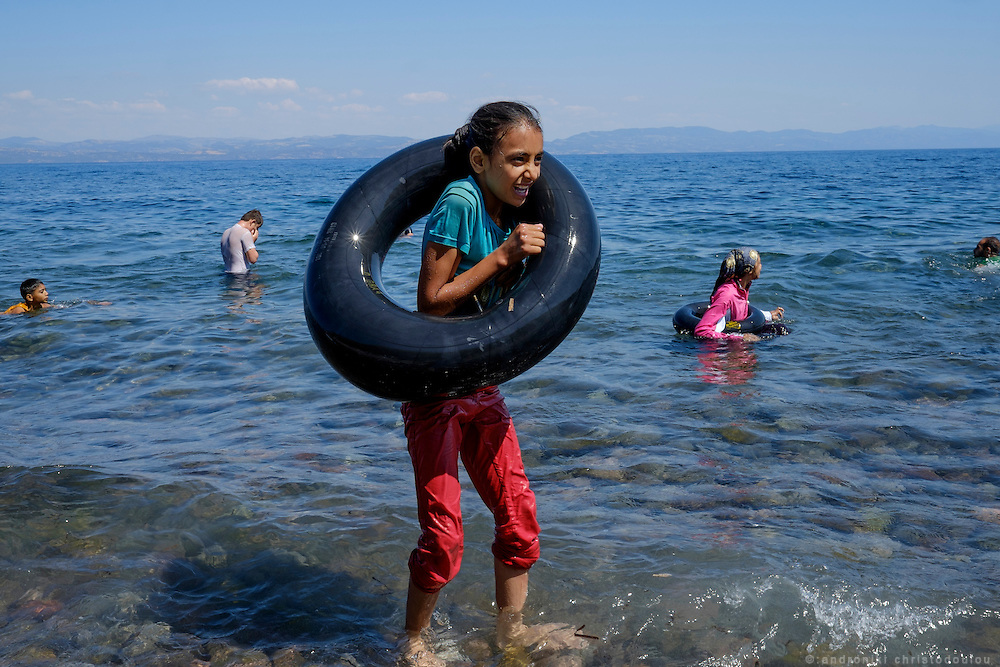 After a safe arrival, some times refugees enjoy some moments of relaxation, taking photos  on their mobile phones and swimming in the sea. <br /> Refugees arriving on beaches near Molyvos village in Lesvos island. Thousands of them come from Turkey, crossing the sea border on inflatable dinghy boats, on a dangerous trip that has claimed many lives. Local people or NGOs expect them and help them in some places but after their arrival, most of them have to walk to the nearest village where they can hope for a places on busses that can take them to the city of Mytilene where they can register and eventually board on a ferry to Athens. Many decide to walk the distance as the busses aren&rsquo;t enough to accommodate the large number of people that arrive daily.