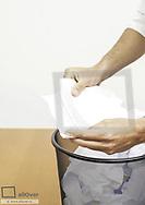 Mann liest zerknuellten Brief aus Papierkorb (model-released)