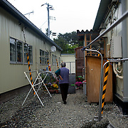 May 29, 2013 - Togura, Japan: A displaced woman walks by prefabricated houses used as temporary shelter for families who lost their homes during the devastating earthquake and tsunami that hit the east coast of Japan in 2011. On the third anniversary of the disaster, nearly 270,000 remain displaced. (Paulo Nunes dos Santos)