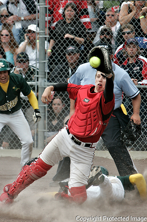 Canada's Derek Arsenie takes a late throw as Australia's Heath Wells slides into home to win the gold medal at the Junior Men's World Fast Pitch Championship on Sunday at the Pepsi Softball Centre in Whitehorse. Australia won 2-1 in extra innings. See story on page 8.