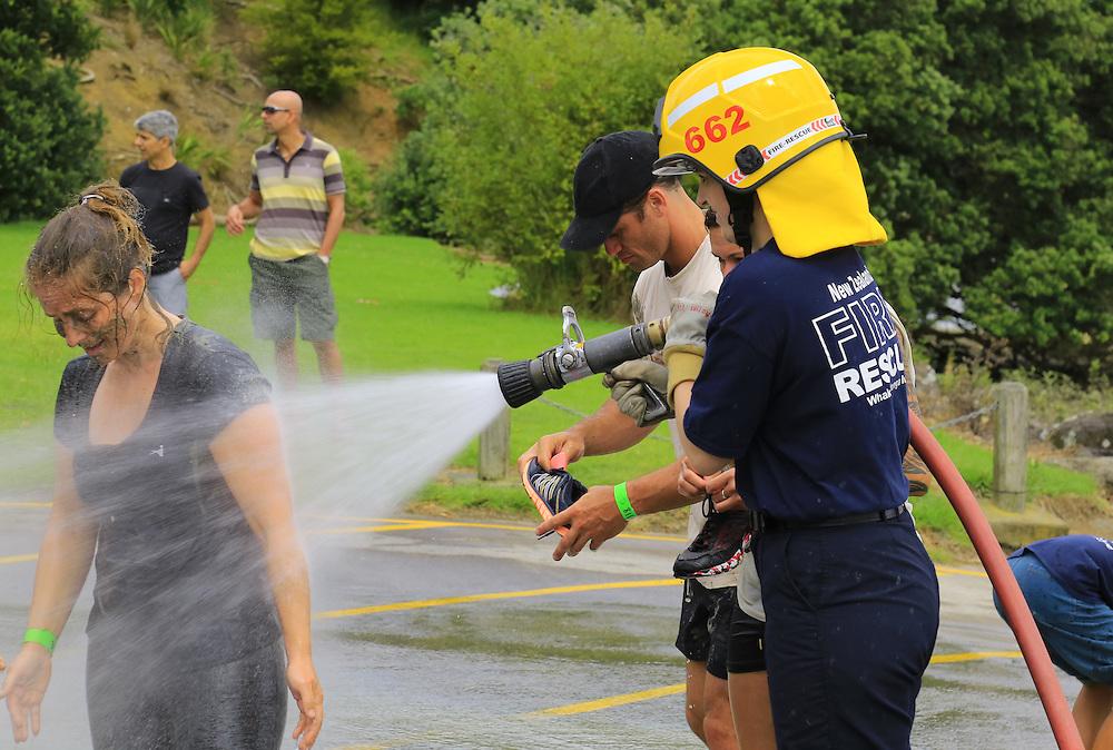 Firemen wash down muddy competitors after a fun run through the mud on Henderson Creek, Te Atatu, Auckland, New Zealand, Sunday, March 06, 2016. Credit:SNPA / Hayden Woodward