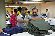 Mohammad (right), assistant  general manager for Epyllion Group, on the factory floor looking at some of the clothes in production.