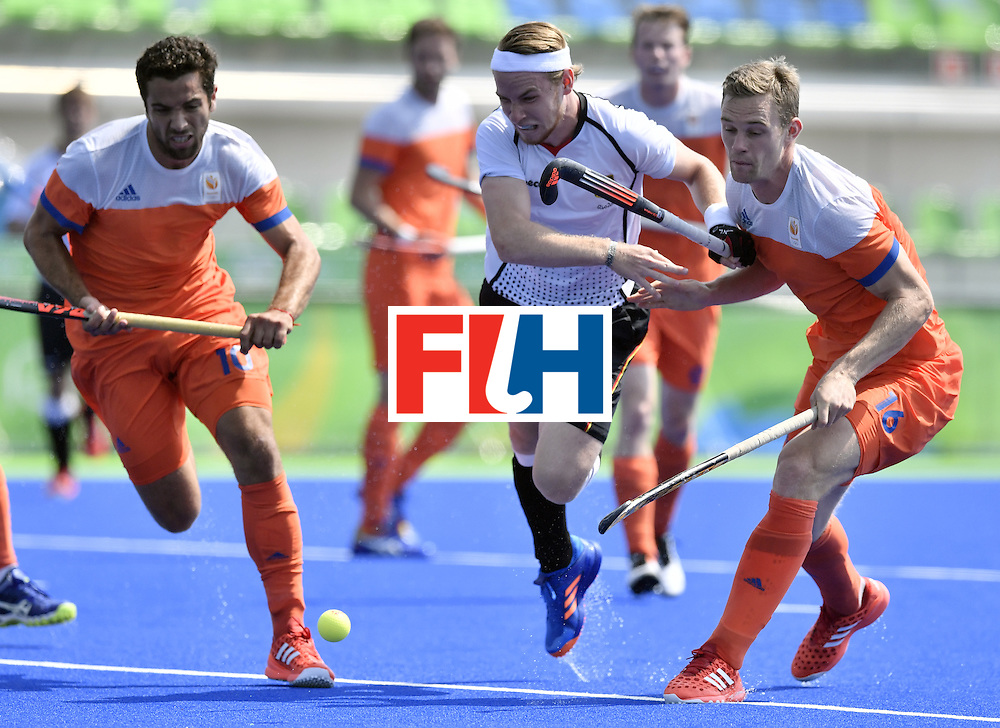 Germany's Christopher Ruhr (C) vies with Netherlands' Valentin Verga (L) and Netherlands' Mirco Pruijser during the men's Bronze medal field hockey Netherlands vs Germany match of the Rio 2016 Olympics Games at the Olympic Hockey Centre in Rio de Janeiro on August 18, 2016. / AFP / PHILIPPE LOPEZ        (Photo credit should read PHILIPPE LOPEZ/AFP/Getty Images)
