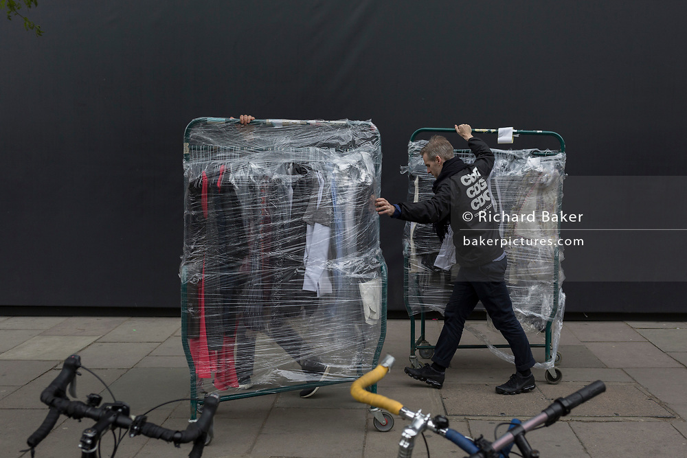 Workmen deliver events clothes wrapped in polythene, on 4th May 2017, in London, England.