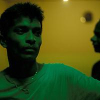 Sri Lanka, Worker under green lights in restaurant along west coast.