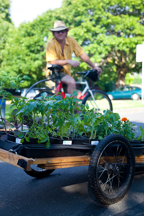 American Center for Sustainability members Scott Allison (yellow shirt) and Danny Bowers sell plants by bicycle in Ladd's Addition, one of the oldest residential districts in Portland, Oregon.