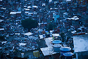 A resident overlooks his neighborhood from the rooftop of his house at the Rocinha slum in Rio de Janeiro, Brazil, Wednesday, Nov. 28, 2012. Although Rocinha is technically classified as a neighborhood, many still refer to it as a favela. It developed from a shanty town into an urbanized slum. In November 2011, a security operation was executed where hundreds of police and military patrolled the streets of Rocinha to crackdown on rampant drug dealers and bring government control to the neighborhood.