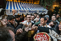 "NAPLES, ITALY - 8 DECEMBER 2017: Waiting customers and pedestrians reach out to the free pizzas offered by Gino Sorbillo (39, center), a Master Pizzaiuolo (pizza chef) and owner of Pizzeria Gino Sorbillo,  together with his brother Toto (right) and a pizzaiuolo (left), to celebrate the art of Pizzaiuolo added to Unesco's list of Intangible Cultural Heritage of Humanity, here by his pizzeria in Naples, Italy, on December 8th 2017.<br /> <br /> On Thursday December 7th 2017, UNESCO added the art of Neapolitan ""Pizzaiuolo"" to its list of Intangible Cultural Heritage of Humanity.<br /> <br /> The art of the Neapolitan 'Pizzaiuolo' is a culinary practice comprising four different phases relating to the preparation of the dough and its baking in a wood-fired oven, involving a rotatory movement by the baker. The element originates in Naples, the capital of the Campania Region, where about 3,000 Pizzaiuoli now live and perform. Pizzaiuoli are a living link for the communities concerned. There are three primary categories of bearers – the Master Pizzaiuolo, the Pizzaiuolo and the baker – as well as the families in Naples who reproduce the art in their own homes. The element fosters social gatherings and intergenerational exchange, and assumes a character of the spectacular, with the Pizzaiuolo at the centre of their 'bottega' sharing their art.<br /> <br /> In Naples, pizza makers celebrated the victory by giving away free pizzas."