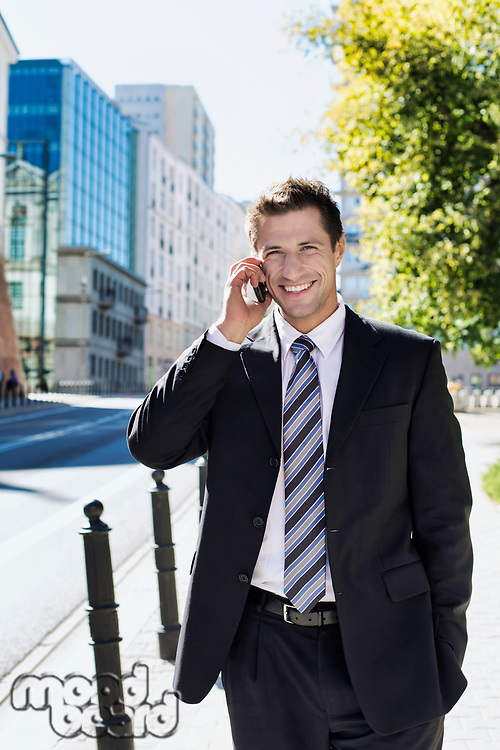 Portrait of mature confident businessman smiling and talking on smartphone while walking on pavement