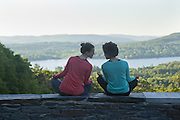 Two women meditating on a stone wall, overlooking a lake.