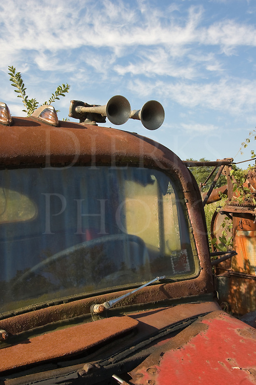 Abandoned rusty truck tractor in a junkyard, a weathered and worn White Mustang from the fifties with air horns and marker lights.
