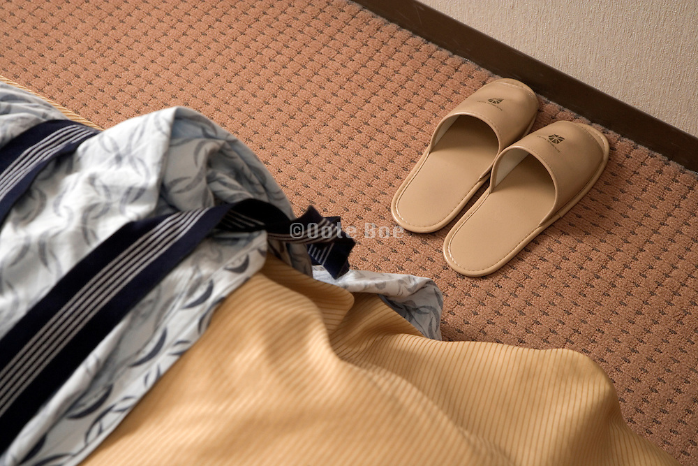 slippers at the end of bed in a Japanese hotel