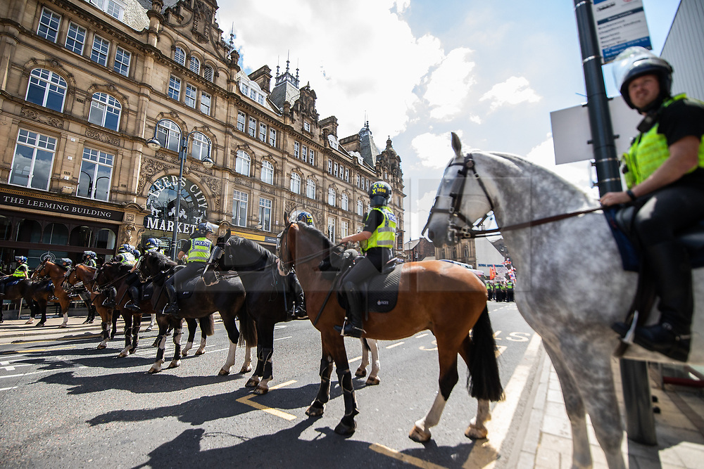 "© Licensed to London News Pictures . 07/07/2018 . Leeds , UK . Mounted police on Boar Lane . An anti-Islam demonstration by supporters of jailed EDL founder Tommy Robinson , including those from the "" Yorkshire Patriots "" and "" First for Britain "" , in Leeds City Centre , opposed by anti-fascists . Robinson ( real name Stephen Yaxley-Lennon ) was convicted of Contempt of Court in May 2018 after committing a second offence , whilst serving a suspended sentence for the same crime . Photo credit : Joel Goodman/LNP"