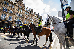 """© Licensed to London News Pictures . 07/07/2018 . Leeds , UK . Mounted police on Boar Lane . An anti-Islam demonstration by supporters of jailed EDL founder Tommy Robinson , including those from the """" Yorkshire Patriots """" and """" First for Britain """" , in Leeds City Centre , opposed by anti-fascists . Robinson ( real name Stephen Yaxley-Lennon ) was convicted of Contempt of Court in May 2018 after committing a second offence , whilst serving a suspended sentence for the same crime . Photo credit : Joel Goodman/LNP"""
