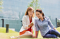 Businesswoman laughing while showing smartphone to her colleague