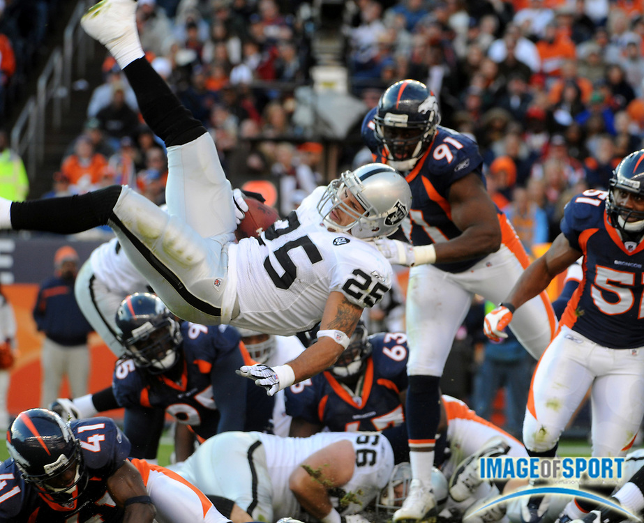 Nov 23, 2008; Denver, CO, USA; Oakland Raiders running back Justin Fargas (25) is upended by Denver Broncos cornerback Karl Paymahn (41) in the first half at Invesco Field. The Raiders defeated the Broncos 31-10.