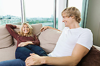 Relaxed couple looking at each other on sofa at home