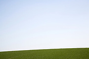 Abstract landscape view blue sky slice of foreground green field, Suffolk, England, UK
