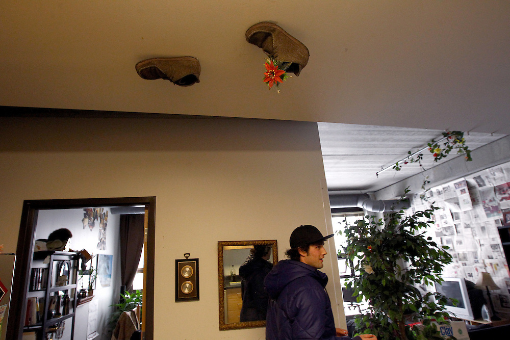3/7/11 3:27:50 PM -- Minneapolis, MN, U.S.A.---.Stephen Bona, 21, of St. Paul, MN, walks under a pair of shoes taped to the ceiling in the highly personalized apartment he shares with three other students in the chemical-free StepUP housing at Augsburg College in downtown Minneapolis March 7, 2011..---.Photo by Courtney Perry, Freelance.