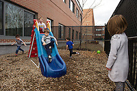 Keegan Connelly and Finn Butler on the slide while Ryder Woodall, Lucas McSheffrey and Jayda Joyce run around in the outdoor playground area of Huot Technical Center Daycare on Wednesday afternoon.   (Karen Bobotas/for the Laconia Daily Sun)