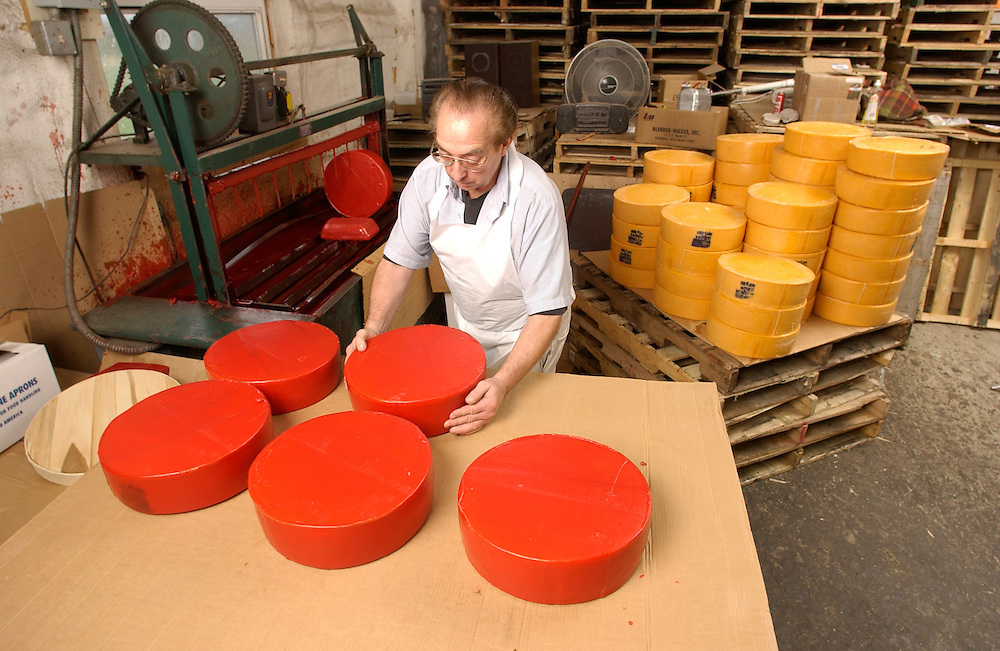Tom Kinjerski works on waxing wheels of cheddar cheese at Renard's Cheese in souther Door County, WI Monday morning May 12, 2003.