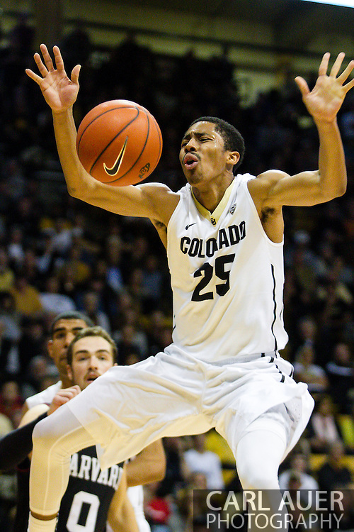 November 24th, 2013:  Colorado Buffaloes junior guard Spencer Dinwiddie (25) loses control of the ball on the way to the basket in the second half of the NCAA Basketball game between the Harvard Crimson and the University of Colorado Buffaloes at the Coors Events Center in Boulder, Colorado