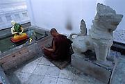 BURMA (Myanmar) - Rangoon (Yangon).A buddhist monk meditates before a sacred shrine at Schwedagon Paya
