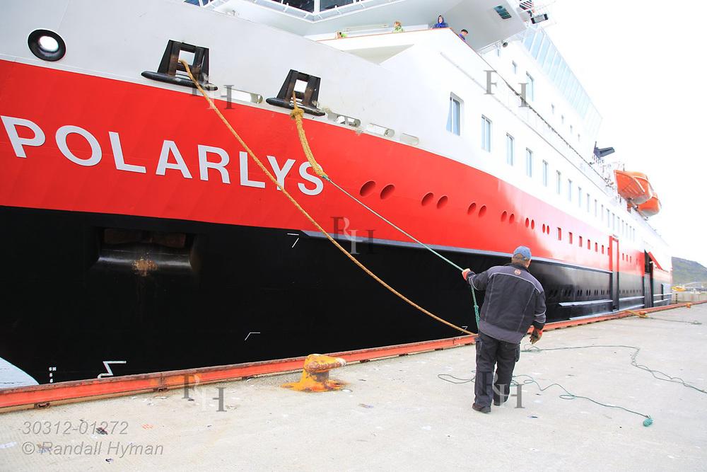 Longshoreman ties Hurtigruten cruise ship, Polarlys, to dock at Havoysund, Norway.